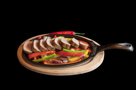 Roast pork medallions with grilled vegetables on a hot pan. The food is isolated on a black background.