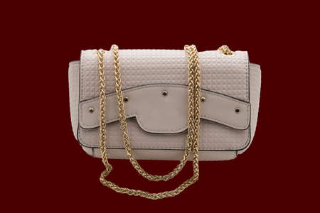 Small women's beige handbag with a gold chain. Photo on a dark background.