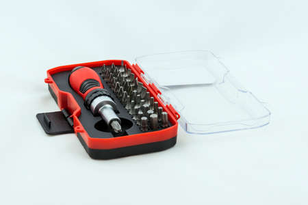 Metal screwdriver and a set of bits in a case. Photo on a white background.