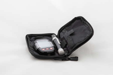 Set for measuring blood sugar. Measuring instrument and pen in a black case. Photo on a white background. 免版税图像