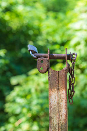 The metal pin on the iron pole is secured with a lock. The photo has a green background. 免版税图像