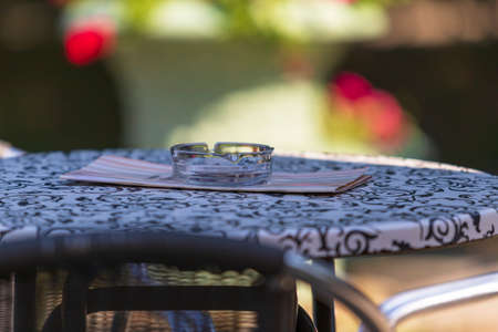 Round table in the garden. There is an ashtray on the table. The background is blurred by photographic technique. The photo has a nice bokeh.