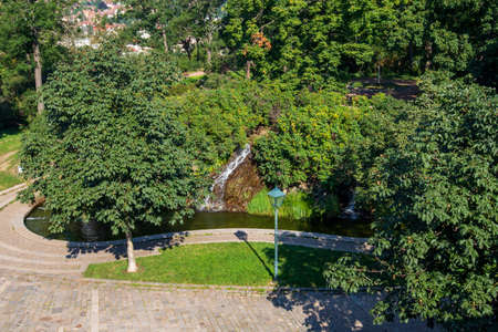 A park with trees and a pond into which a small waterfall flows. Top view. Stock fotó