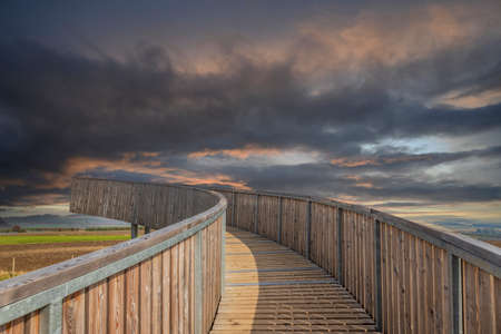 The wooden footbridge leading upwards serves as a lookout tower. In the background are dramatic clouds 版權商用圖片