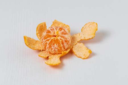 Tangerine in a split peel on a white table.