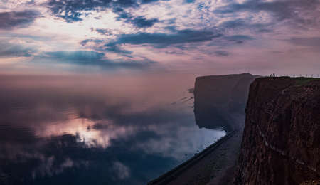 Sunset on Helgoland island in Germany on the top of Long Anna. It is getting dark and there is fog