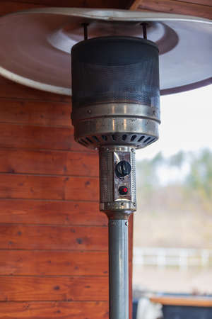 Gas metal air heater for outdoor areas. The heater stands in the garden restaurant.