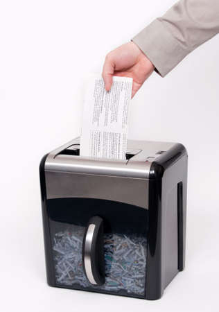 A man putting confidential documents into a paper shredder photo