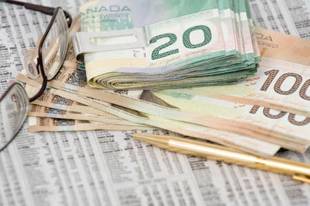 pick money: 20 d�lares canadienses en el clip y billete de 100 d�lares en la parte superior de la bolsa con comillas gafas y la pluma Foto de archivo