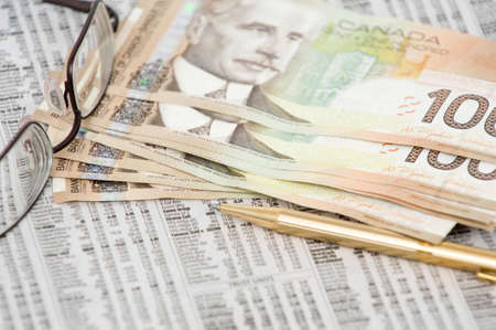 Canadian 100 dollar bill on top of stock market quotes with eye glasses and pen photo