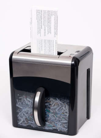 A paper shredder with a confidential document about to be shredded photo