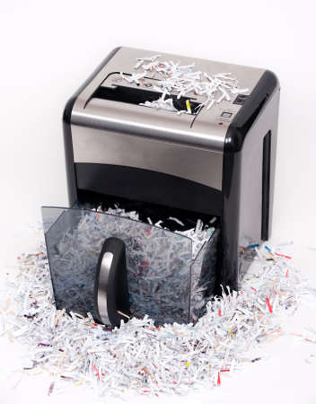 shredder: An open paper shredder with shredded paper all around