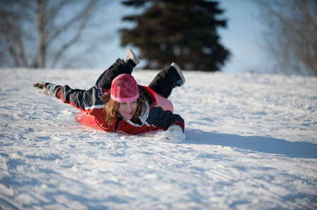 Girl sledding down the tobogganing hill Stock Photo