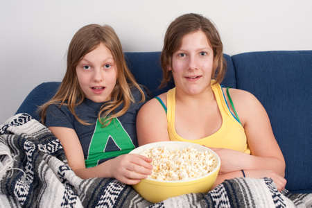 two girls on sofa eating popcorn and watching tv photo