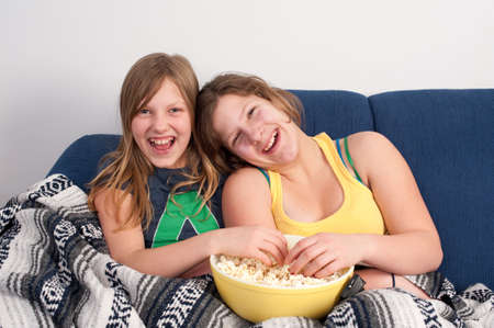 two girls on sofa eating popcorn and watching tv Stock Photo - 4398597