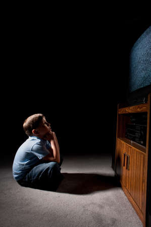tv watching: Six year old boy watching static on television in the dark Stock Photo