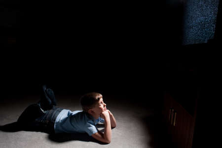 front room: Six year old boy watching static on television in the dark Stock Photo