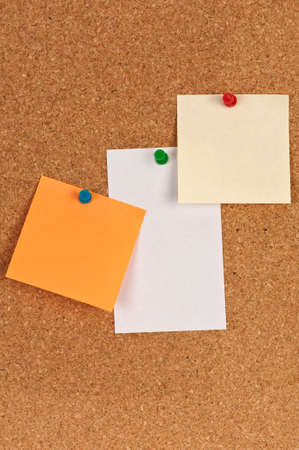 Three pieces of paper on a corkboard photo
