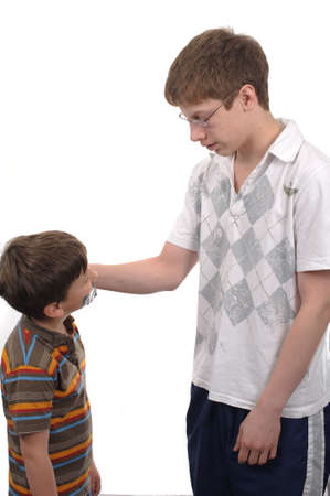Teen boy putting tape on annoying little brother