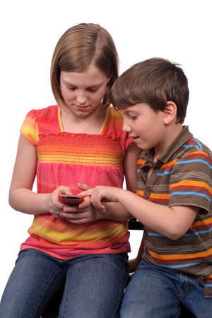 Two young kids texting messages on a smart phone photo