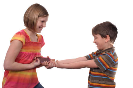 brother sister fight: Two young kids fighting over a cell phone Stock Photo
