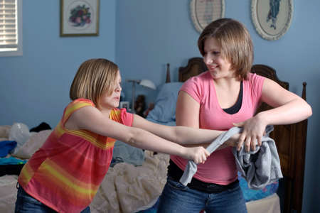 two young sisters fighting over some clothing