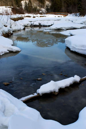 thawing: A river thawing in early spring with snow around river Stock Photo