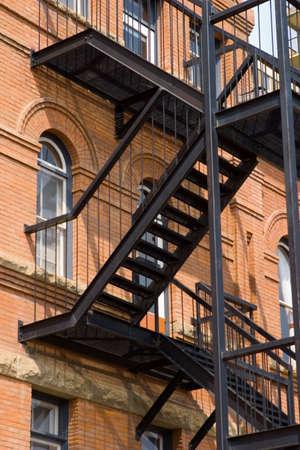 huir: Una escalera de incendio en un viejo edificio de ladrillo