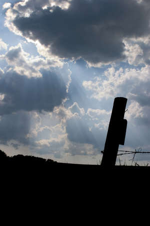 Fence posts with clouds in the background photo