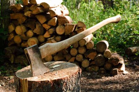 Een bijl vast in een log boek voor een stapel hout
