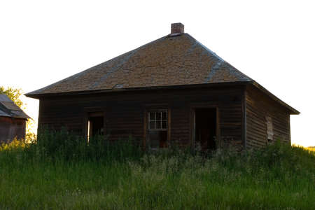An old run down farm house with weeds around it Stock Photo - 6097726