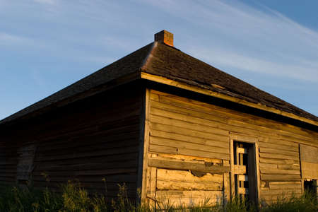 An old weathered building with the sun shining on it Stock Photo