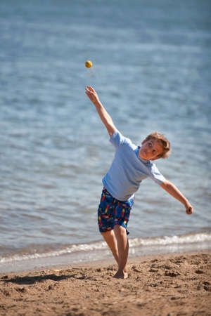 A seven year old boy throwing a ball photo