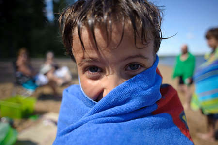 A seven year old boy drying off from swimming photo