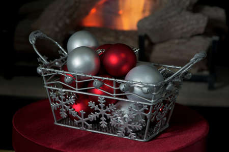 Red and silver christmas balls in a basket in front of a fire photo