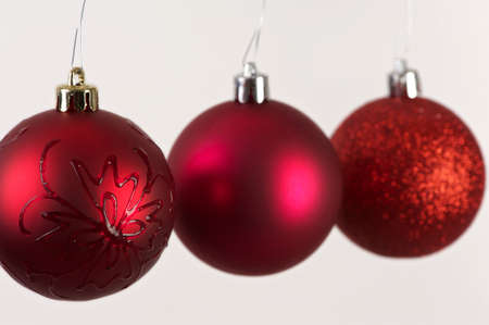 Three red christmas balls hanging close together with shallow depth of field