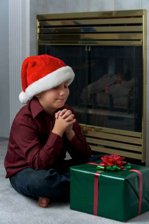 A young boy wishing or praying for a good gift photo