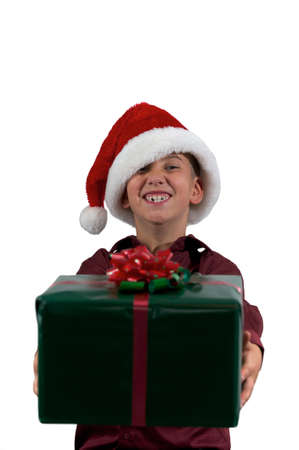 An eight year old boy in a santa hat giving a present  to you on isolated background photo