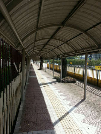 beside: Covered walkway beside a road Stock Photo