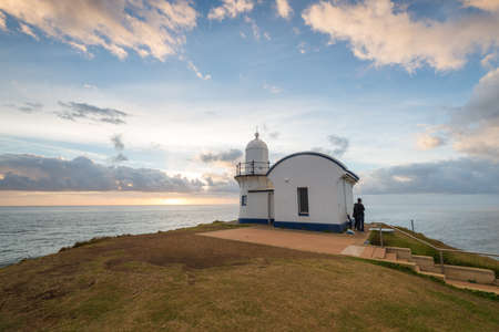 Tacking Point Lighthouse sunrise with people looking sunset. Port Macquarie, NSW, Australia. Stock Photo