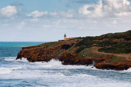 Seascape at the ruins roman of tipasa with Rough sea. Lighthouse on the coast