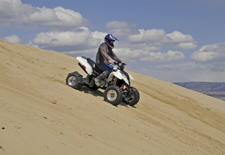 quad: man riding sport quad done a sand mountain Stock Photo