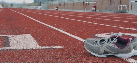 track with running shoes in lane, ready for practice Banco de Imagens