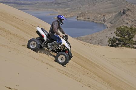 quad: man riding sand dune mountain on sport quad