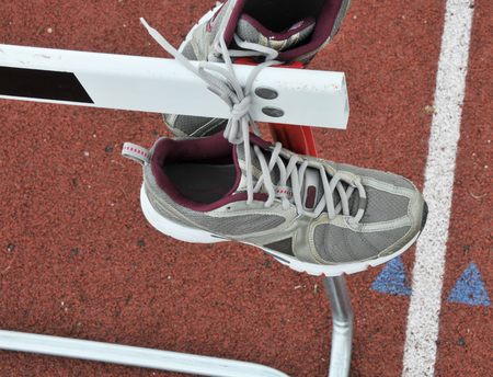 hurdle: Track Shoes thrown over hurdle on track