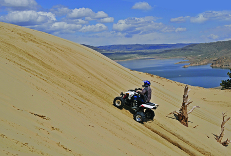 quad: man riding sport quad up a sand mountain with lake in background