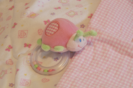 recieving: pink baby lady bug rattle resting on flannel recieving blankets Stock Photo