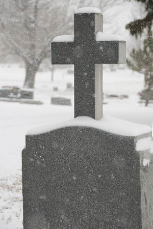 cemetary: snow covered tombstone with cross in cemetary Stock Photo