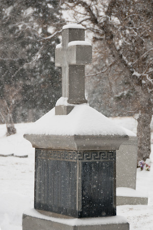 snow covered tombstone with cross in cemetary Banco de Imagens