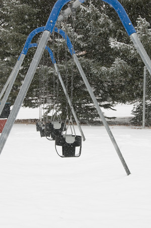 swing set: Swing set seat in cold weather with snow and ice Stock Photo